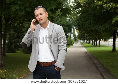 Businessman on the street with smart phone  - stock photo