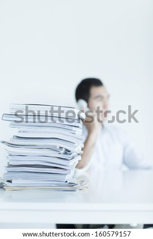 Businessman on the with stack of papers on desk - stock photo