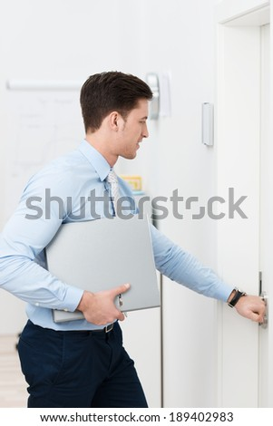 Businessman opening a door as he leaves the office with a binder under his arm - stock photo