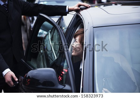 Businessman opening car door for businesswoman - stock photo