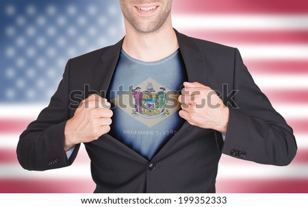 Businessman opening suit to reveal shirt with state flag (USA), Delaware - stock photo