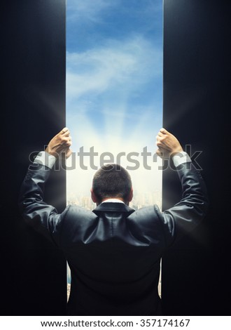 Businessman opening the gate to a bright light of cityscape - stock photo