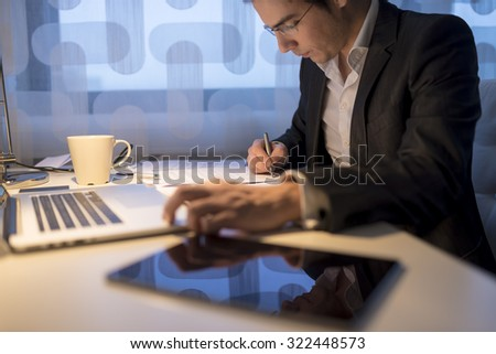 Businessman or lawyer, working late business hours with  laptop, digital tablet and coffee on his office desk as he completes his work with signing a final document, focus to the pen. - stock photo