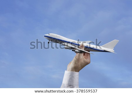 Businessman or Person Holding Model Airplane in a Blue Sky - stock photo