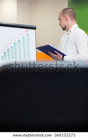 Businessman or team leader giving a lecture or presentation to his work colleagues in the office standing pointing to a flipchart with diagrams - stock photo