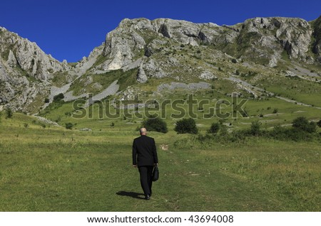 Businessman oudoors walking through a big mountain.The main focus is on the rocks,the man is slighty out of focus. - stock photo