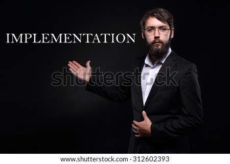 "Businessman over black background presenting ""Implementation"" - stock photo"