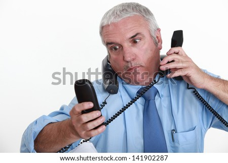 businessman overwhelmed with phone calls - stock photo