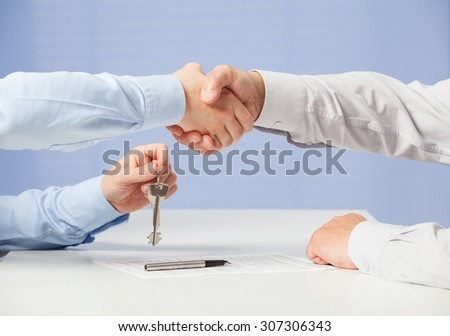 Businessman passing keys to his partner and shaking his hand, blue background - stock photo