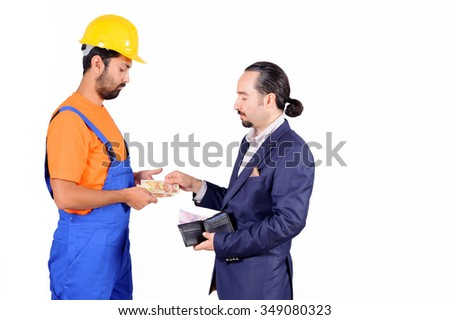businessman paying hired blue collar laborer for services isolated on white background. - stock photo