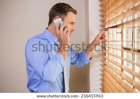 Businessman peeking through blinds while on call in office - stock photo