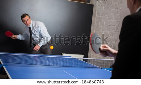 Businessman play tennis with opponent in office - stock photo