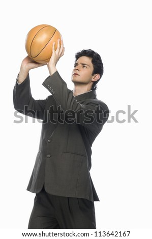 Businessman playing basket ball - stock photo