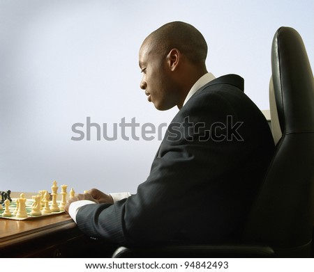 Businessman playing chess in office - stock photo