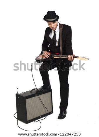 Businessman playing guitar with one leg on the amplifier against white background - stock photo