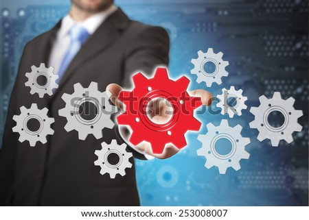 Businessman playing with gears and various cogwheels - stock photo
