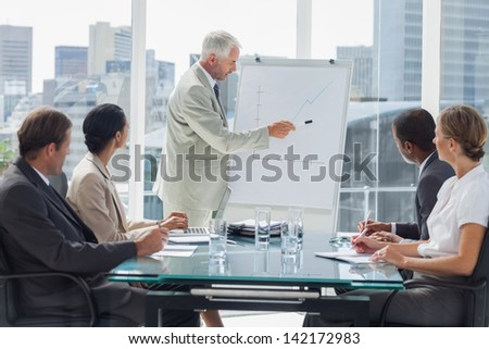 Businessman pointing at a growing chart during a meeting with people listening to him - stock photo
