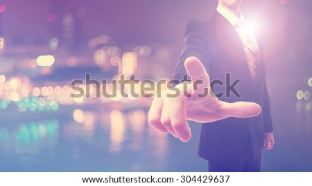 Businessman pointing at something on blurred city background - stock photo
