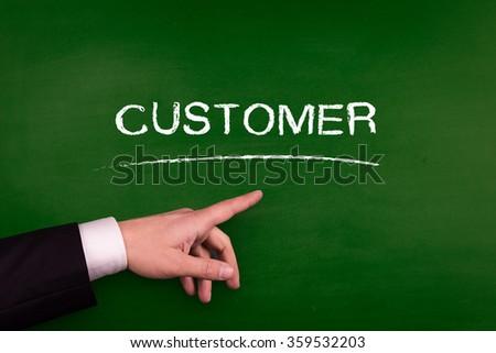 Businessman pointing CUSTOMER word on blackboard - stock photo