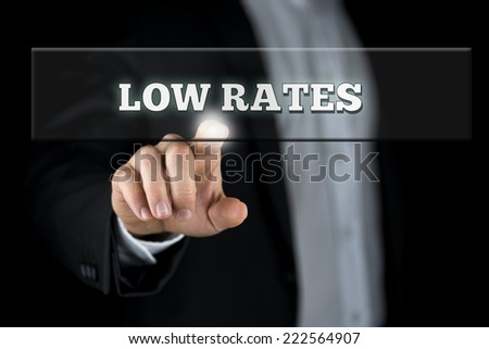 Businessman Pointing Low Rates Texts on Transparent Box. Isolated on Black Background. Common to Banking Concepts. - stock photo