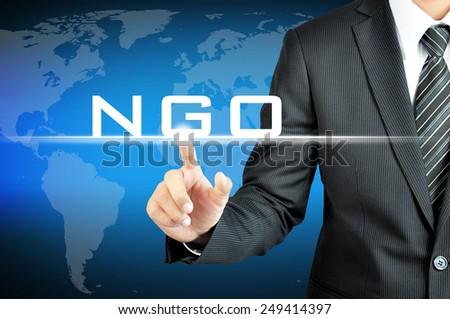 Businessman pointing on NGO (Non-Governmental Organization) sign on virtual screen - stock photo