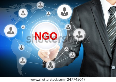 Businessman pointing on NGO (Non-Governmental Organization) sign on virtual screen with people icons linked as network - stock photo