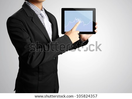Businessman pointing on touch screen tablet in a hand - stock photo