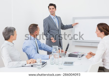 Businessman pointing the white screen in the office - stock photo