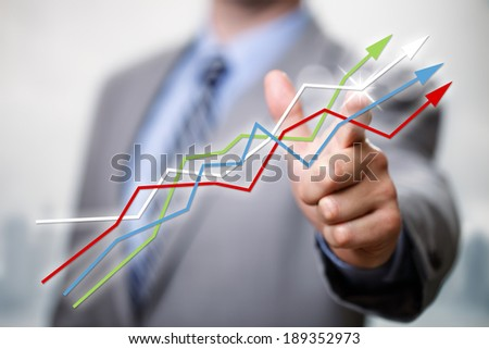 Businessman pointing to growth in a line graph showing business success - stock photo