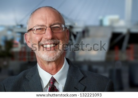 Businessman posing to the camera on plaza in the urban area. - stock photo