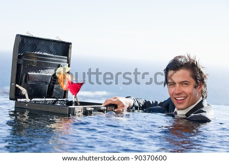 Businessman posing with a cocktail in a briefcase in a swimming pool - stock photo