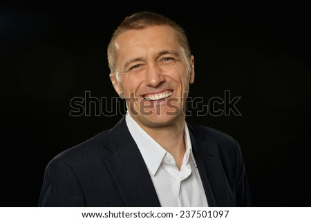 Businessman posing with smiling on a black background - stock photo