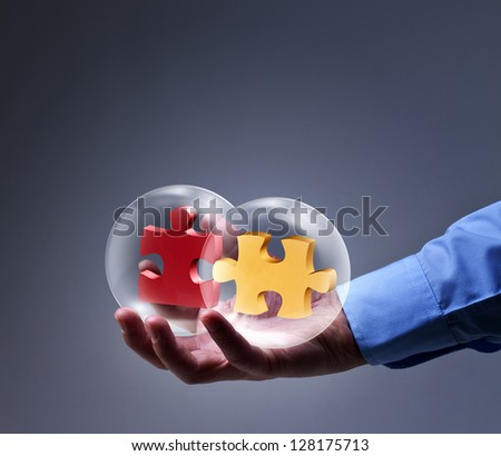Businessman presenting a brand new solution - two puzzle pieces in glass spheres - stock photo