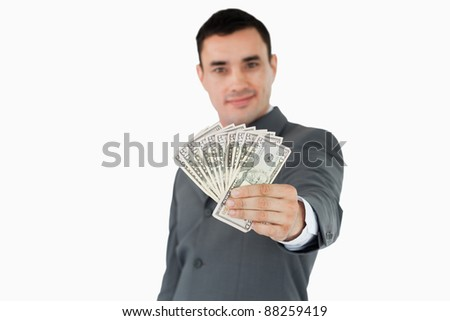 Businessman presenting bank notes against a white background - stock photo
