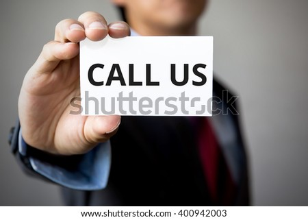 Businessman presenting 'Call Us' word on white card - stock photo