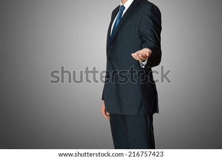 businessman presenting something on grey background - stock photo