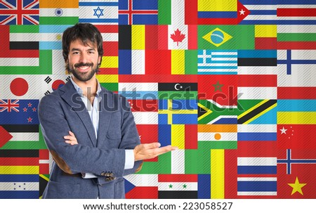 Businessman presenting something over flags background - stock photo