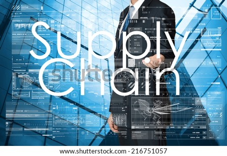 businessman presenting Supply Chain text, graphs and diagrams with skyscraper in background, business concept - stock photo