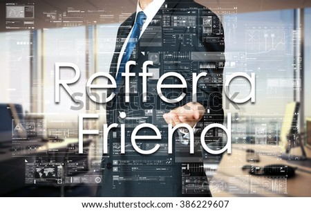 Businessman presenting text Reffer a Friend on virtual screen. He is in the office - stock photo
