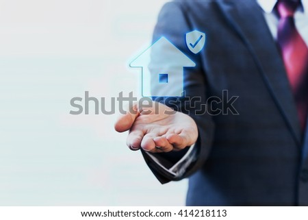 Businessman presenting virtual house with protection on his palm of hand - house insurance concept - stock photo