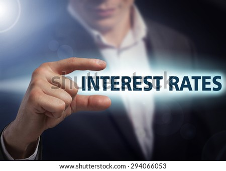 Businessman presses button  interest rates on virtual screens. Business, technology, internet and networking concept. - stock photo