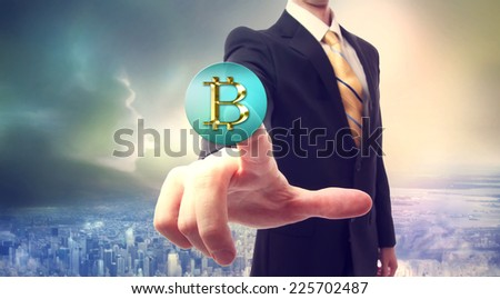 Businessman pressing a Bitcoin button over big city background - stock photo