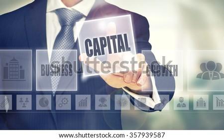 Businessman pressing an Capital concept button. - stock photo