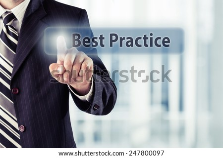 Businessman pressing Best Practice button at his office. Toned photo. - stock photo