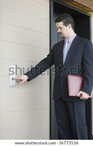 Businessman pressing button for elevator in an office building - stock photo