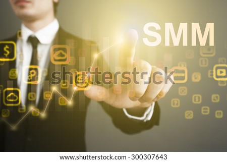 """Businessman pressing button on the virtual screen and select """"SMM"""". business concept. Internet concept. - stock photo"""