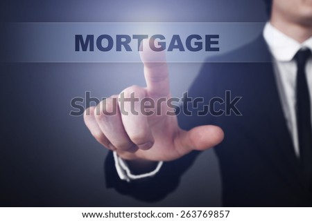 Businessman pressing button on touch screen interface and select  mortgage. Business concept. - stock photo