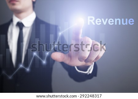 Businessman pressing button on touch screen interface and select revenue. business concept. - stock photo