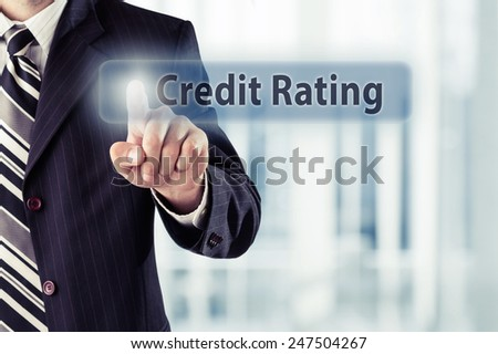 Businessman pressing Credit rating button at his office. Toned photo - stock photo
