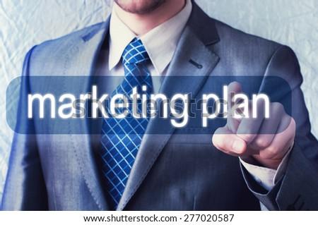 Businessman pressing Marketing plan button on virtual screen - stock photo